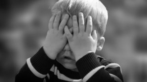 photo of child with hands covering his face